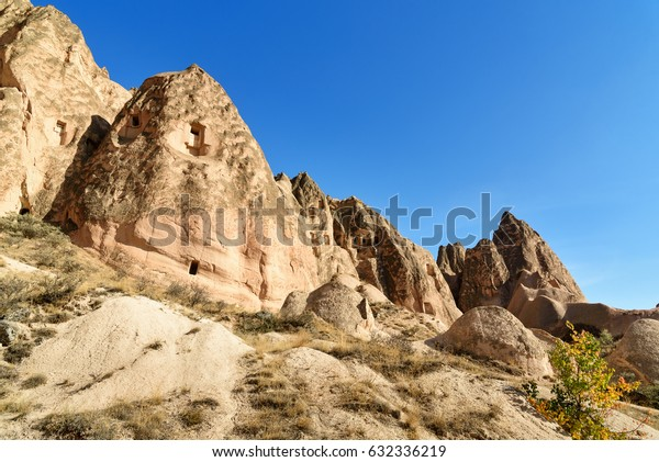 View of cave houses in mountain formations in valley at Cavusin. Cappadocia. Nevsehir Province. Turkey