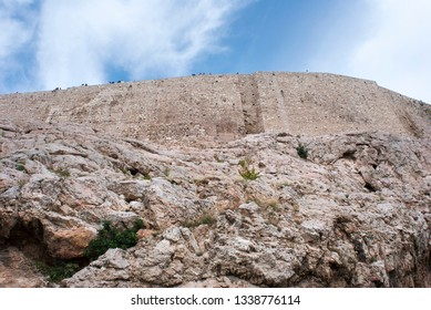 The view of caves and rocks with Acropolis of Athens wall on a top built in 5th century BC (Greece).