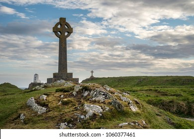 View of Celtic Cross on Ynys Llanddwyn Island in Angelsey with Twr Mawr Lighthouse in background landscape