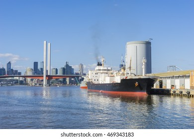 View of cement carrier with bridge and modern buildings in the background during daytime