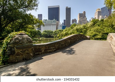 View of Central Park South from Gatstow Bridge. The bridge spans The Pond on a quiet morning in Central Park springtime.