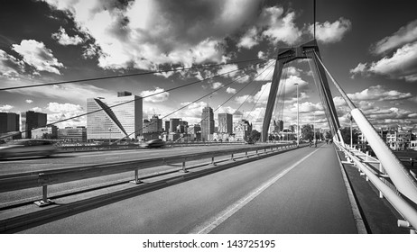 A view of central Rotterdam and the famous Wilemsbrug bridge, the Netherlands. Black and white photograph with dramatic clouds.