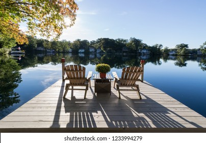 View of chairs and dock on a pristine lake with reflections and shadows