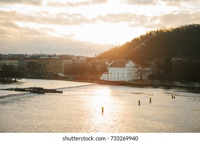 View from the Charles Bridge in Prague at sunset - old architecture, hill with trees, river and birds against sky. Czech Republic