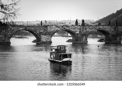 View of the Charles Bridge, Vltava River and small excursion boat. Black and white shot. Vintage.