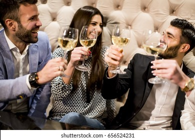 View at cheerful group of young people toasting with white wine