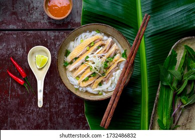 To view of Chicken pho or Pho ga on a street food restaurant in Hanoi, Vietnam. Including chicken, fresh rice noodle, herb on broth. Special Vietnamese food famous in the World