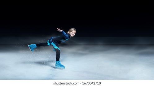 view of child  figure skater on dark ice arena background