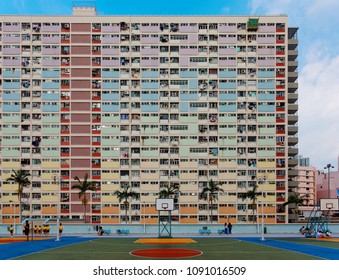 View of Choi Hung public housing estate in Kowloon, with school boys & girls playing in the basketball court & crowded narrow apartments in the building, a phenomenon of housing shortage in Hong Kong