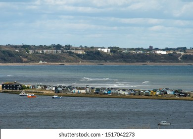 view of Christchurch Harbour UK with row of colourful beach huts on Hengistbury head with gorgeous sky.
