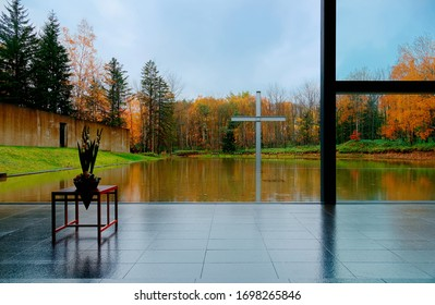 """View of a Christian cross surrounded by fall colors & reflected in a pool through the floor-to-ceiling window of """"Church on the Water"""", a famous architecture by Tadao Ando, in Tomamu, Hokkaido, Japan"""