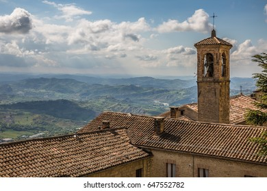 view of church belfry with cross on roof against a majestic mountain landscape and dramatic tender cloudy blue sky background in San Marino, Italy, Europe