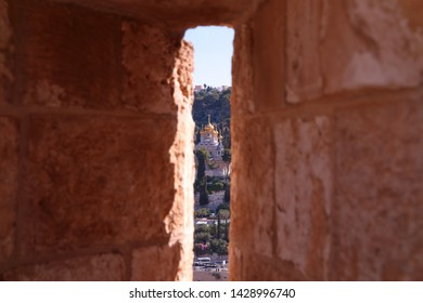 View at a Church of Mary Magdalene - Russia style church with golden cupola - through the arrow slit of a wall of Jerusalem Old City, Israel