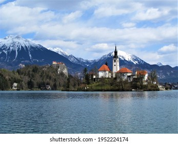 View of the church on the island on lake Bled and Bled castle and snow covered peaks of Karavanke mountains with mountain Stol behind in Gorenjska, Slovenia - Shutterstock ID 1952224174