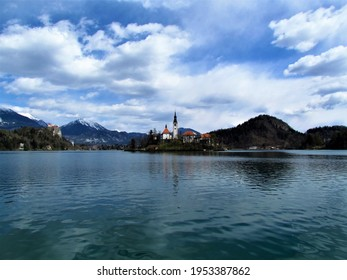 View of the church on the island on lake Bled and Bled castle and snow covered peaks of Karavanke mountains with mountain Stol behind in Gorenjska, Slovenia - Shutterstock ID 1953387862