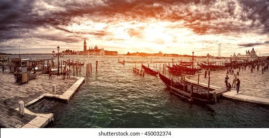 A view of the Church of San Giorgio Maggiore on the island of the San Giorgio Maggiore with gondolas parked in the water canal on Riva degli Schiavoni in Venice, Italy.