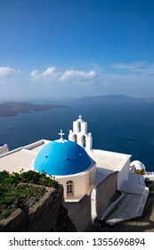 A view of a church in Santorini, overlooking the ocean.