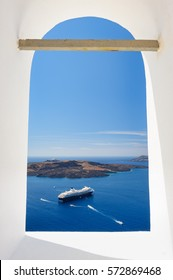 View from church's window in Fira town to the caldera sea with ships and volcano island. Santorini, Greece. Copyspace.