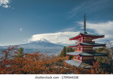 View from Chureito Pagoda in autumn, Fujiyoshida, Japan. There are many trees with red and orange color leaves. Fuji volcano in the back with snow on the peak on the clear sky. Copy space on top.