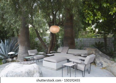 View of circular lamp over outdoor garden furniture by trees