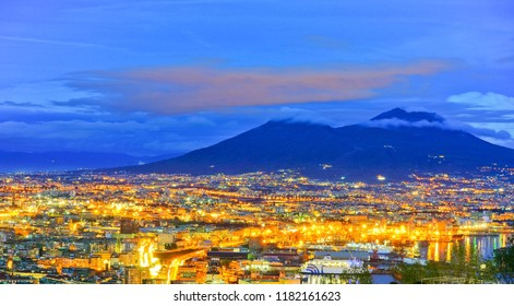 View of the city center of Naples and Mount Vesuvius along the Gulf of Naples at night in Naples, Italy.