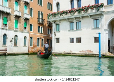 View of the city Grand Canal in Venice in a sunny day. Gondolier driving the gondola with tourists. Venice, Italy