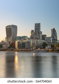 View of The City of London during sunset with reflection in the Thames river.