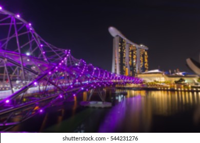 View of city night lights at Helix Bridge,Marina Bay Sands hotel light show.singapore travel landmark blurred bokeh background.