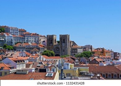 The view of the city from view point on a sunny summer day. The roofs of the houses.  The Lisbon Cathedral Santa Maria Maior de Lisboa or Se de Lisboa. Portugal.