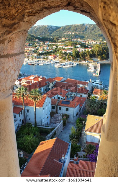 View of the city of Rab through the lookout window at summer sunset in Croatia. Scenic cityscape of Rab.