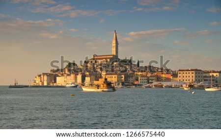 View of the city of Rovinj in Croatia. Sunset shot of the old town from harbour, showing boats basking in golden light