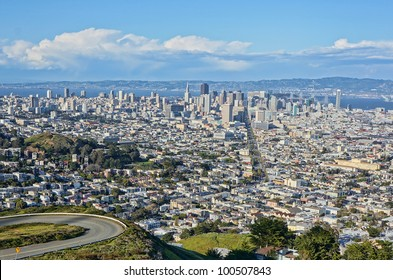 View of the city of San Francisco from Twin Peaks on a sunny day with clouds.