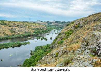 View of the city Yuzhnoukrainsk and Southern Bug river, Ukraine. Landscape of the river with island with greenery. Rocky coast of the river. - Shutterstock ID 1128980651