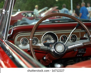 View from classic red convertible through windshield at a car show