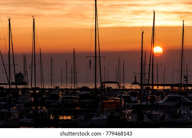 A view of a classic sunset nestled among boats with the Lorain Harbor Lighthouse to the left along Lake Erie in Lorain, Ohio.