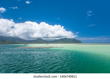 View of the clear turquoise waters of Kaneohe Bay as seen from the iconic sandbar in Oahu, Hawaii with the famous Chinamen's Hat rock formation island in the distance.