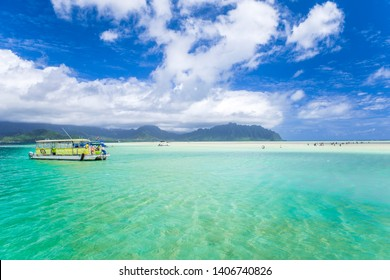 View of the clear turquoise waters of Kaneohe Bay as seen from the iconic sandbar in Oahu, Hawaii with the famous Chinamen's Hat rock formation island in the distance. - Shutterstock ID 1406740826
