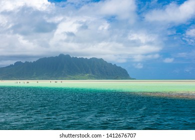 View of the clear turquoise waters of Kaneohe Bay as seen from the iconic sandbar in Oahu, Hawaii with the famous Chinamen's Hat rock formation island in the distance. - Shutterstock ID 1412676707