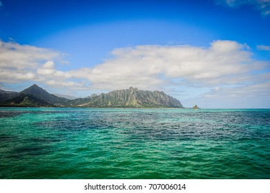 View of the clear turquoise waters of Kaneohe Bay as seen from the iconic sandbar in Oahu, Hawaii with the famous Chinamen's Hat rock formation island in the distance