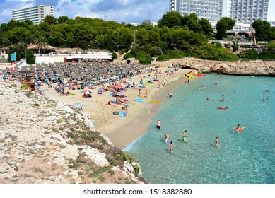 View from a cliff to a sandy beach with clear water and a sunny blue sea with tourists bathing in a bay on the island of Mallorca in the Mediterranean Sea. Spain, Calas de Mallorca