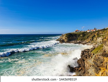 View of cliff top villas and the Atlantic ocean waves on a sunny summer day, taken in Praia das Maçãs, Sintra, Portugal