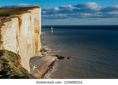 View of the cliffs of Birling Gap and the lighthouse on Seven Sisters National Park in The United Kingdom on a sunny day with clean blue sky
