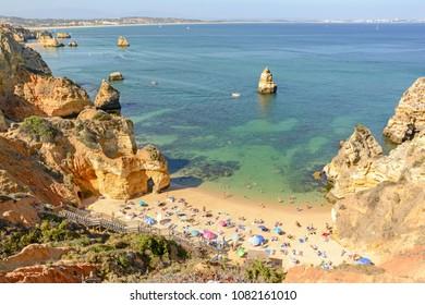 View from the cliffs to busy beach Praia do Camilo near Ponta da Piedade, Lagos Algarve Portugal