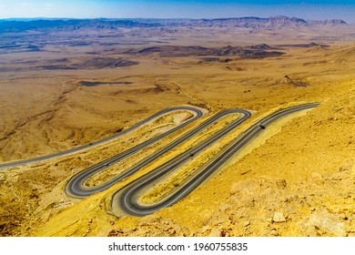 View of cliffs, landscape, and hairpinned road in Makhtesh (crater) Ramon, the Negev Desert, Southern Israel