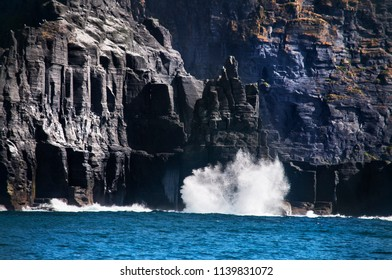 View of the cliffs of Moher from the ocean. Waves crashing against the rocky shore.