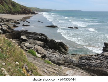 A view from the cliffs on the west end of Tregantle beach and Whitsand bay in Cornwall, looking east across sweeping white waves towards the Rame head peninsular and Plymouth in Devon.