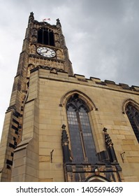view of the clock tower and building of the historic saint peters parish church in the center of huddersfield against a cloudy sky