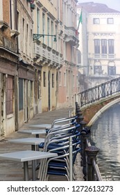 View to a closed restaurant in the foggy canals and streets of Venice.