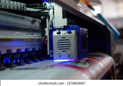 view of  Closeup of Large Inkjet printer in working with multicolor cmyk colors on vinyl banner