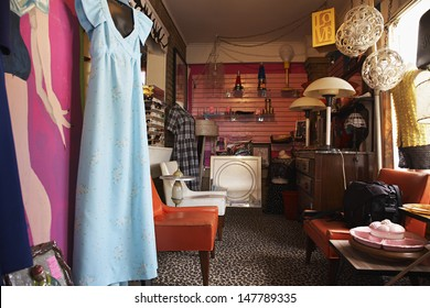 View of clothing and furniture in crowded second hand store
